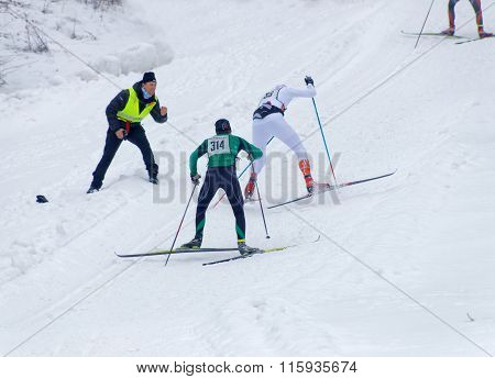 Two Cross Country Skiing Men Sprinting Uphill, One Is Falling