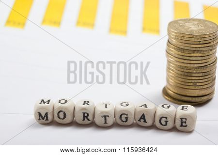 MORTGAGE word written on wood block, golden coins and chart