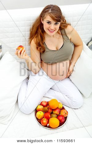 Smiling beautiful pregnant woman sitting on sofa and holding fruit in hand