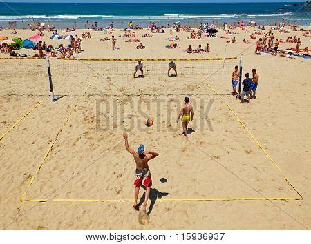 Youngs Mens Playing Volleyball In Zurriola Beach, San Sebastian. Spain.
