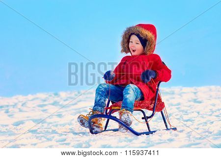 Happy Kid Sliding Downhill On Winter Snow