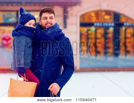 Father And Son On Winter Holiday Shopping In City, Buying Presents