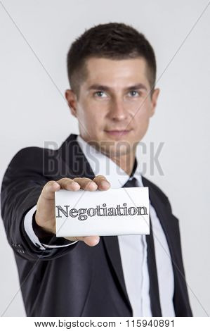Negotiation - Young Businessman Holding A White Card With Text