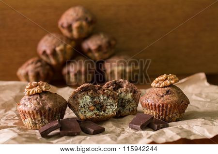Bicolor muffins with chocolate, poppies and walnuts on paper