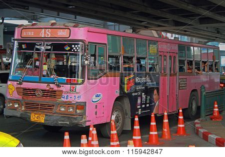 people are riding in pink bus