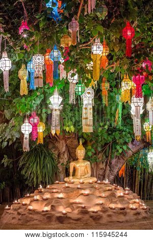 Buddha statue surounded by candles during Loy Kratong Festival, Wat Pan Tao Temple, Chiang Mai, Thailand.