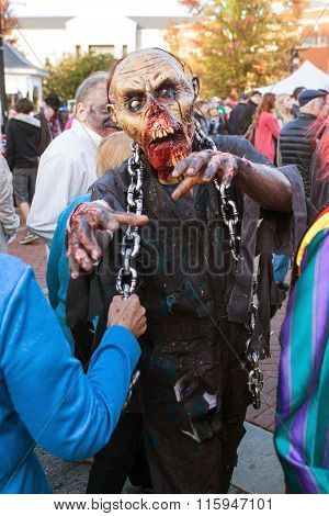 Man In Terrifying Zombie Mask Menaces People At Halloween Festival