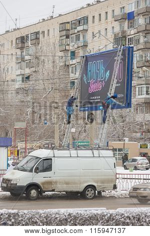 """Employees Of The Advertising Agency Paste Banner On A Street Billboard """"night Sale"""""""