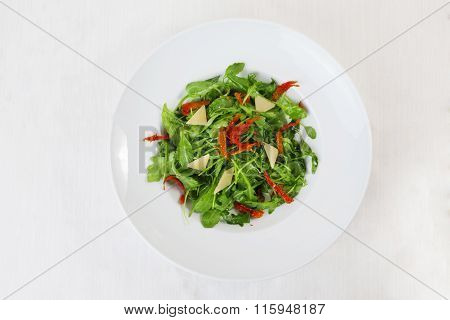 arugula salad dried tomatoes parmesan top circular plate white background isolated