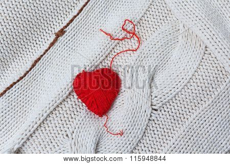 Red heart of red yarn on a background of knitted sweaters. Love