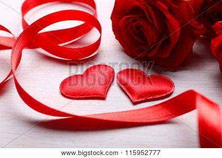 Two Hearts, Ribbon And Red Roses On Table