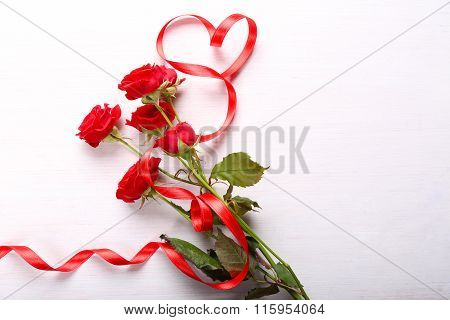 Red Roses And Ribbon On Table