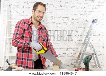 Smiling Young Man Cutting A Board With A Hand Saw