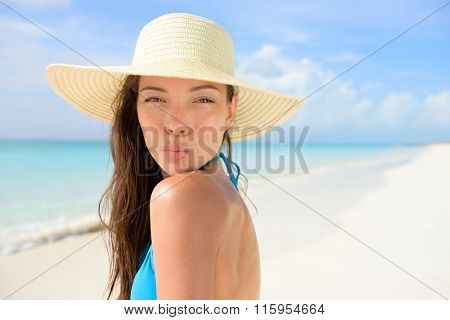 Beach sun hat woman blowing cute kiss on vacation. Asian female young adult model striking a kissing pose to the camera for summer holidays wearing straw sunhat and blue bikini on perfect white sand.