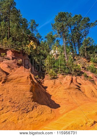Unique red and orange hills in the province of Roussillon, France. Coniferous forests create a beautiful contrast with the color of ocher