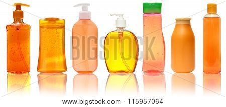 Seven orange  Plastic Bottles With Shampoo, Liquid Soap, Shower Gel. Isolated on white background wi