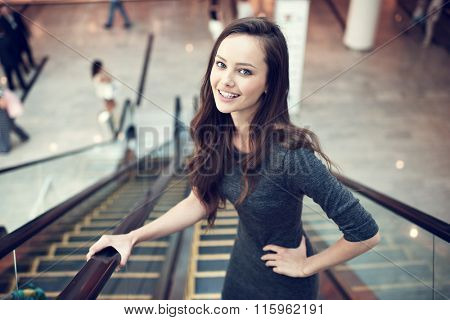 Outdoor portrait of the beautiful young sexy woman. Attractive caucasian  girl smiling and posing in the shop. Pretty female person with positive emotions