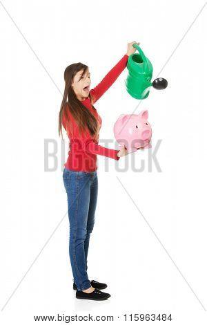 Woman watering piggybank.