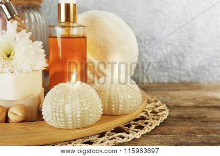Variety of natural bath tools on wooden table, on grey wall background