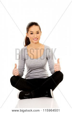Woman sitting cross legged with thumbs up.