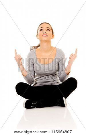 Woman sitting cross legged pointing up.