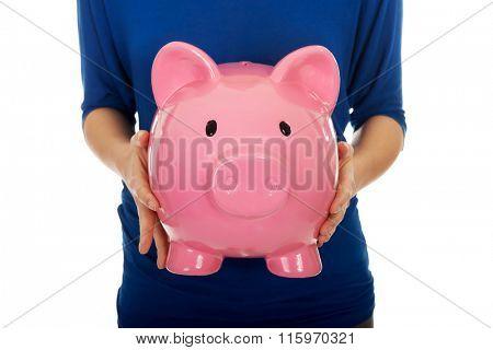 Woman holding piggybank.