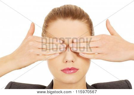 Businesswoman covering eyes with hands.