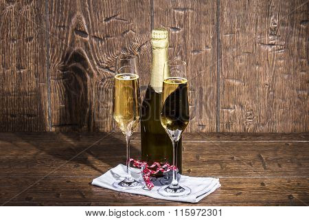 Bottle And Two Glasses Of Champagne Are Standing On A White Napkin On Old A  Table