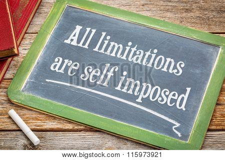 all limitations are self imposed - inspirational statement on a  blackboard with a white chalk and a stack of books against rustic wooden table