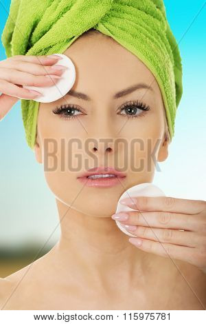 Beautiful woman with cotton pads.