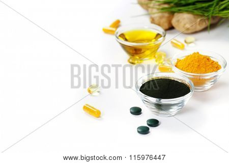 Alternative natural medicine. Dietary supplements. Spirulina, turmeric  and organic oil on white background. Superfood, detox or diet concept. Background layout with free text space.