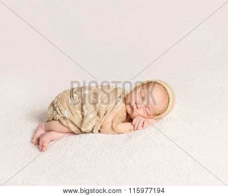 sleeping newborn baby with lovely cheeks in hat covered with a blanket
