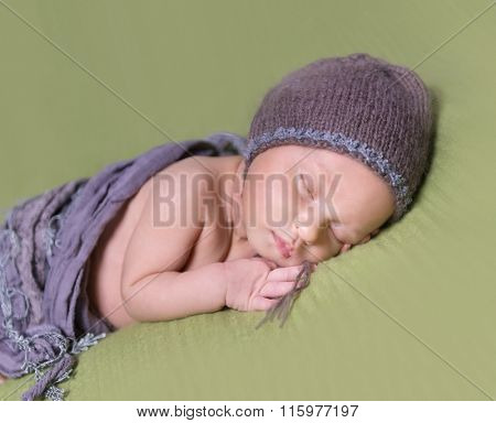 innocent newborn baby with hat sleeping on a blanket