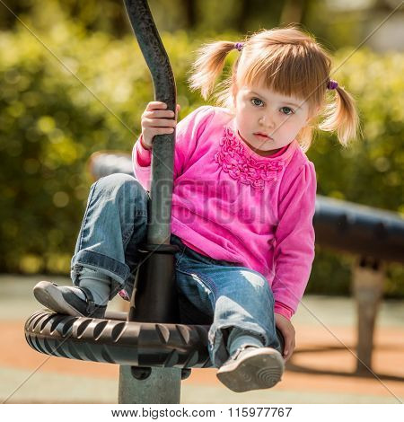 Cute little girl on outdoor playground equipment