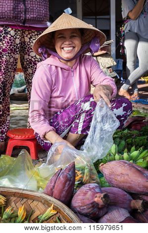 Smiling woman in conical hat at the market