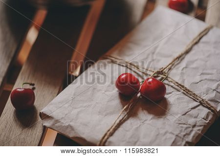 fresh cherries on plate with wrapped gift on wooden table.
