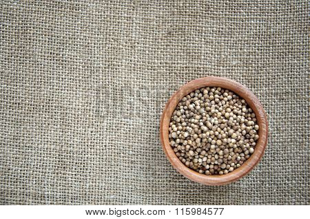 Coriander In A Wooden Bowl On Burlap Background