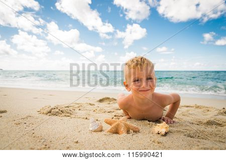 Little Boy Playing With A Starfish On The Beach
