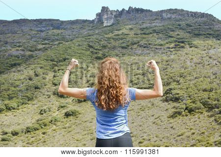 Girl Flexing Muscles On A Mountain Top