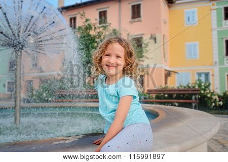 child girl relaxing at fountain in Izola (Isola) city in Slovenia.