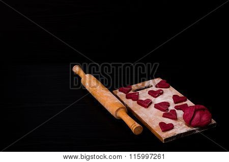 Raw Red Heart-shaped Cookies And Dough On Wooden Board With Flour, Wooden Rolling Pin. Black Backgro