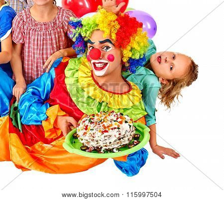 Cheerful male clown with cake on kids birthday with group children. Isolated.