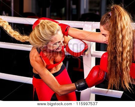 Two  women boxer with long hair wearing red  gloves to box in ring.