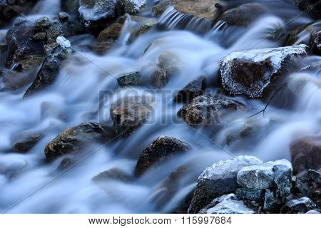 mountain stream among frozen stones at winter time