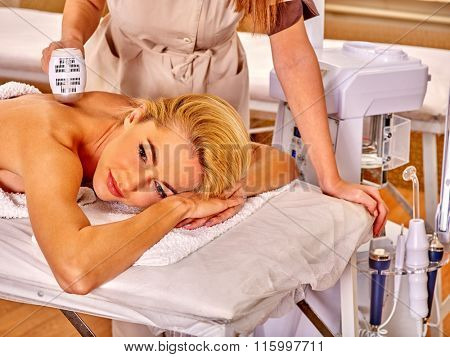 Young woman receiving electric back massage on microdermabrasion equipment at  hardware cosmetology beauty salon.