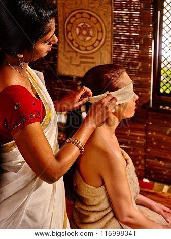 Young woman having head ayurveda treatment at India spa.