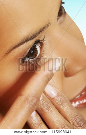 Woman inserting contact lens