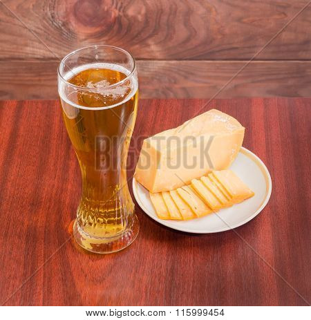 Beer Glass With Lager Beer And Cheese On Saucer