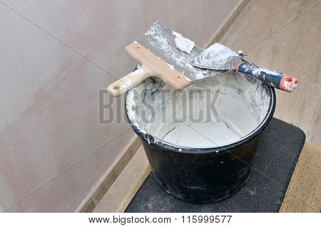 spatulas and stucco in a bucket closeup