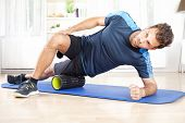 Athletic Man In Side Planking Using Foam Roller poster